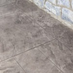 tan stamped concrete pattern with gray fieldstone wall