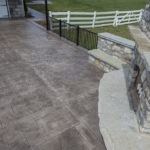 stamped concrete patio with fieldstone fireplace